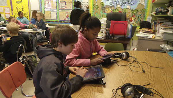 Isabella Ellis and Grant Patterson, students of Dana Hill at U.S. Jones Elementary, are shown playing interactive math games on iPads made possible by the classroom grants program.