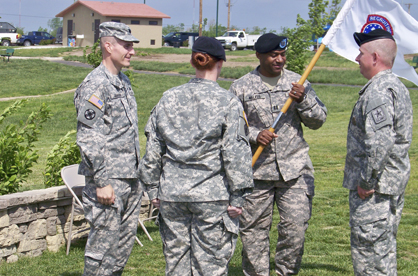 Capt. Major Walker III returns the guidon to 1st Sgt. Jefferson Paul, signifying a change in leadership. The ceremony took place at Cunningham Park in Joplin, Mo.