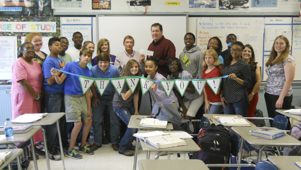 Jeff McAfee of Jackson Newell Paper recently presented a $1,000 check to support the Demopolis City Schools Foundation's 2013 Membership Campaign to Kim Townsend, vice president of the Foundation's board of directors while visiting with Ashley Brock's eighth-grade science class at Demopolis Middle School. McAfee shared some inspirational words with the class about continuing their education and discovering their strengths.