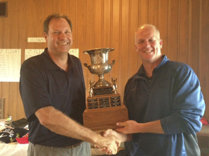 Rotarian and Tournament Organizer Bill Meador (left) presents the winner's trophy to Paul Garner of Selma, who won the Rotary Charity Golf Tournament for the second year in a row.