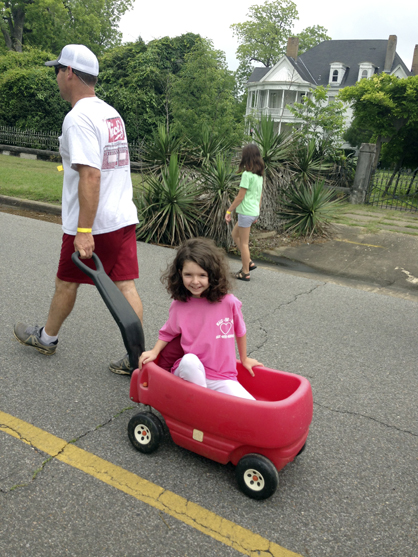 Anna Coleman rode in her wagon for part of the mile. She is being pulled above by Chip Hughes, whose daughter Allie played T-ball with Anna Coleman, while talking with her mom.