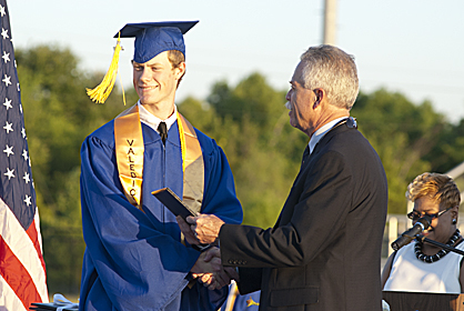 Chance Martin, class valedictorian, receives his diploma from principal Leon Clark on Friday evening.