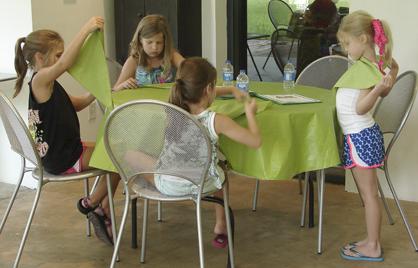 Girl campers practice folding napkins.