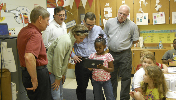 Kim Townsend, DCSF vice president and membership committee chair, looks on as a student shows her favorite math applications to CEMEX employees Anne Saelens, Al Giles, James Burden and Gary Pinault during a visit to Elizabeth Renner's second grade class.