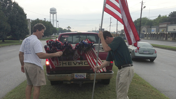 Kiwanis Club President Craig Schumacher and club member Johnny Brooker place an American Flag along Highway 80 for Independence Day.