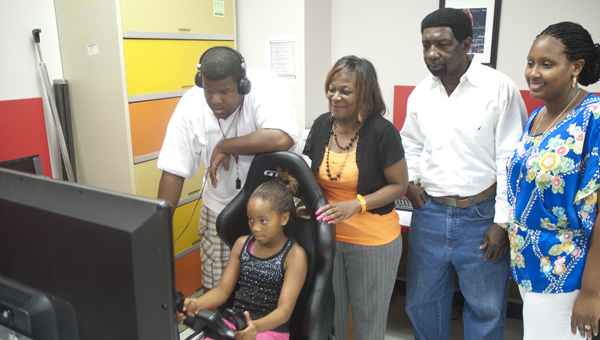 Josh Rowser, Barbara Wallace, Edward Ward and Bridget Glover help Serenity Johnson use the Theo Ratliff Activity Center's flight simulator during a lesson Thursday afternoon.