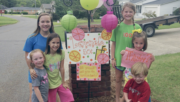 Six children opened a lemonade stand Friday afternoon at Marengo Drive with the proceeds going to Amanda Harrison and her family. Shown left of the sign are Anna Causey, Kelsey Causey and Ellie Kaye Meadows; and right of the sign are Abby Grace Cameron, Riley Windham and Bryce Meadows.