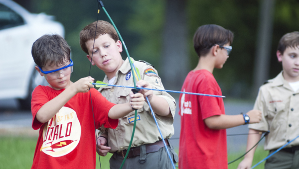 Daniel Thomas, 9, practices archery with help from Boy Scout Joseph Barnes.