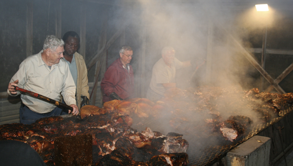 A concrete pit on the grounds of the Jefferson Community Clubhouse is the site for both the annual Jefferson Barbecue and the Jefferson Volunteer Fire Department Barbecue. It's an all-night cooking that requires a team of hard workers. Pictured left to right are Joe Coats, Bobby Daniels, Buddy Lindsay, and George Norris.
