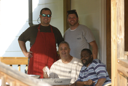 David Compton (seated) batters fish for the club's annual fish fry with the help of Nate Charleston (seated), Dave Compton (left) and Tony Luker (right).
