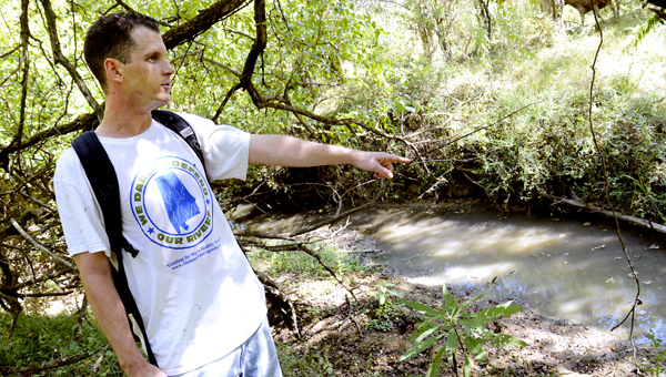 Adam Johnston, Alliance Coordinator with the Alabama River Alliance, points Thursday to a spot where waste water was leaking into Freetown Creek from the Uniontown spray field.