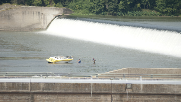A salvage crew works Wednesday to retrieve a ski boat that has been stranded on rocks below the Demopolis dam for more than two weeks.
