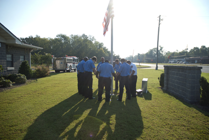 Firefighters gathered around the American flag Wednesday morning to pray and to honor those lost on Sept. 11, 2001.