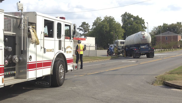 Firefighters clean up from small spill after an empty oil truck jack knifed on Cedar Avenue at Demopolis First United Methodist Church.