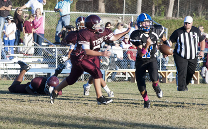 DMS quarterback Andrew Patterson evades tacklers against Thomasville.