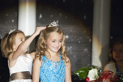 Last year's Little Miss Christmas on the River Taylor Quinney reaches up to crown this year's winner, Meredith Gray Patrenos.