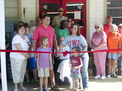 Betsy Compton and Tony Luker, surrounded by family, friends and Jefferson community members, cut the ribbon on the reopened store Saturday.