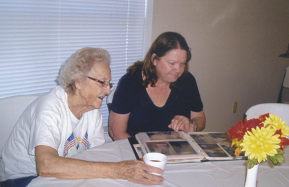 Lois McCarson and Vicki Price look through a photo album of the 20 years of the Riverside Care and Share.