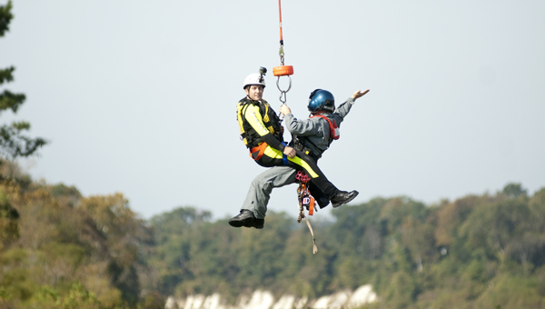 """A """"victim"""" was airlifted to an area below the Demopolis dam so he could be rescued during swift water rescue training Tuesday."""