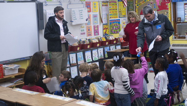 Jay Reynolds tells children in Becky Holley's first grade class about the contest while Lee Pritchett and Suzanne Young hand out stickers to the students.