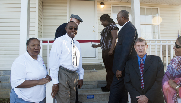 Carolyn Jackson cuts the ribbon in front of her new home on East Fulton Street that was built by Habitat for Humanity.