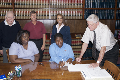 Carolyn Jackson signs closing papers on her new Habitat for Humanity home last Thursday. Shown from left are Dick Kirkpatrick, Terrie Charleston, Kim Townsend, Jackson, Aliquippa Allen and Tom Boggs.
