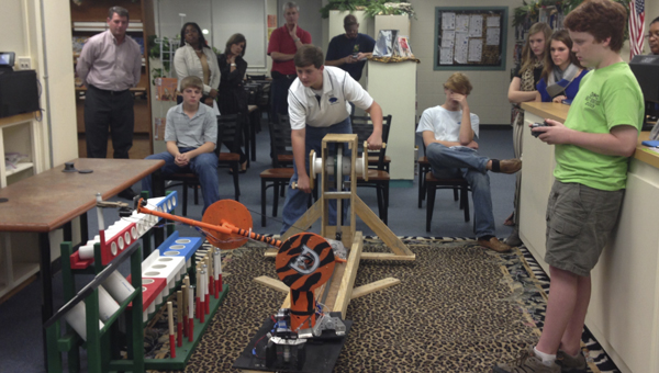 Jordan Durrett (center) and Sean Frankowski (right), members of the DMS Robotics team, demonstrate what their robot can do during Monday evening's board of education meeting.