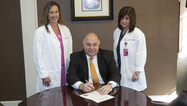Demopolis Mayor Mike Grayson signs a proclamation for Perioperative Nurse Week. He is shown with BWWMH nurse Anna Freeman (left) and nurse manager of the Surgical Services Department Donna Pope (right).