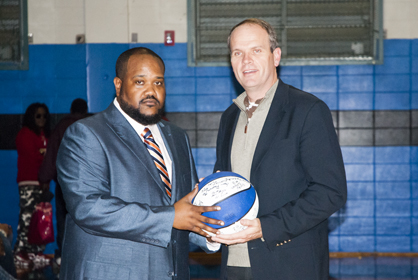 Demopolis boys head coach Rodney Jackson presents a signed basketball to Hunter Compton of Manley, Traeger, Perry and Stapp, thanking them for their support of the program.