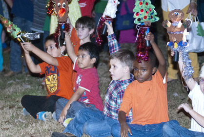 Children from Westside's after school program hold up lanterns they made for the lighting.