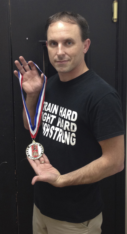 Ross Martial Arts co-owner Jay Russell is shown with a new custom medal that will be awarded during the 2014 Complete Grappling Challenge at the Demopolis High School gymnasium on Saturday, Jan. 25.