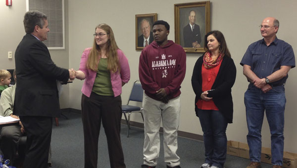 Demopolis Superintendent Dr. Al Griffin presents DMS Robotics teacher Ashley Brock with a resolution honoring the team's accomplishments. They are shown with robotics team member Erin White, team coach Sherri Jones and team coach Jimmy Lee.