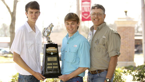 UWA students Andrew Warbington and Mitch Brumbeloe are proud to hold the trophy they brought back to Livingston after Sunday's Carhartt Bassmaster College Classic. The UWA Tiger Bass Club is coached by UWA staff member Doyle Truelove (right).