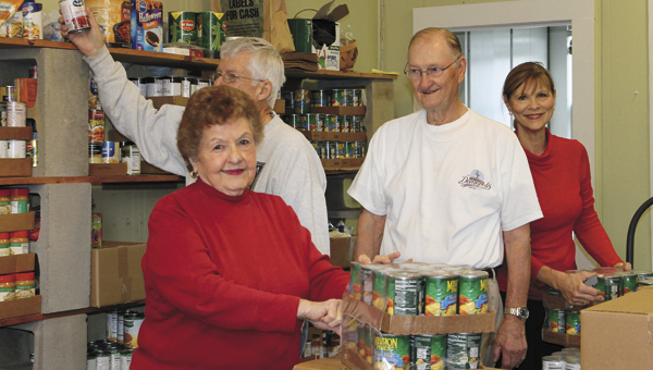 Daphne Glaser, Stan Brasfield, Thomas Melton and Kaye Evans package food for the pantry.