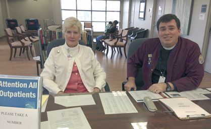 Bryan W. Whitfield Memorial Hospital Auxiliary members Rebecca Culpepper and the Rev. John David Barnes works at the hospital's front desk.