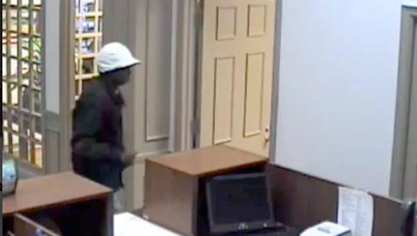 Video surveillance from Robertson Bank shows a man jumping the teller counter and making off with cash.