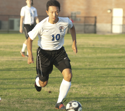 Jeremy Chu brings the ball up the field.