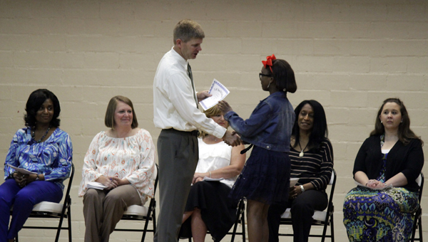 Demopolis Middle School student Aundria Murdock receives an award from DMS principal Blaine Hathcock during the sixth grade awards ceremony Wednesday, May 14.