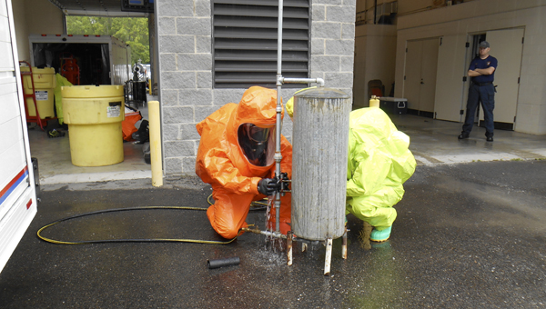 Demopolis Fire Department firefighters work together to fix a leak in a Hazmat training simulation.