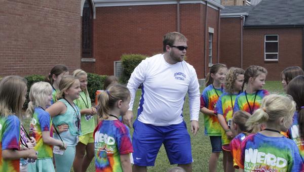 Clay Massey works with children during Demopolis First United Methodist Church's VBS.