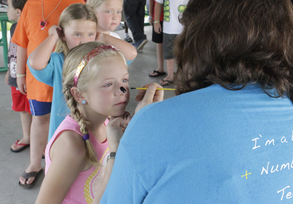 Marley Miller gets her face painted during Demopolis Public Library's outdoor event Monday.