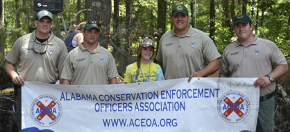 Sara McVay, shown with Alabama game wardens, won a lifetime Alabama hunting and fishing license by winning an essay contest.