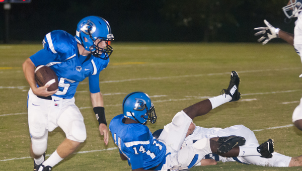 Demopolis quarterback Logan McVay looks for an open hole in Friday night's win over Jemison. McVay ended the game as the Tigers' leading rusher with 94 yards and two touchdowns on three carries.