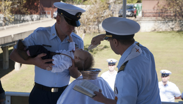 Lucas Coy Hefty, held by his father Mike Hefty, is baptized aboard the USCGC Wedge by Chaplain Dan Berteau.