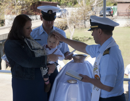 Chaplain Dan Berteau performs the baptism ceremony on Lucas Coy Hefty, who is held by his parents, Mike and Alisha Hefty.