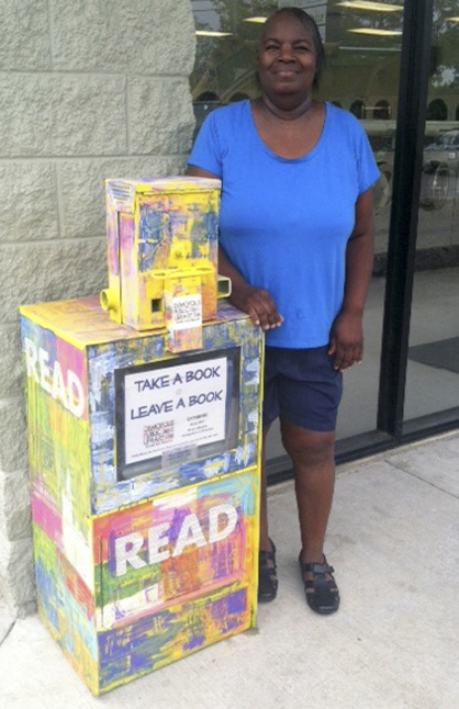 Loretta Wade, who works at Suds By Holiday Cleaners, shows off Demopolis' new Little Free Library.