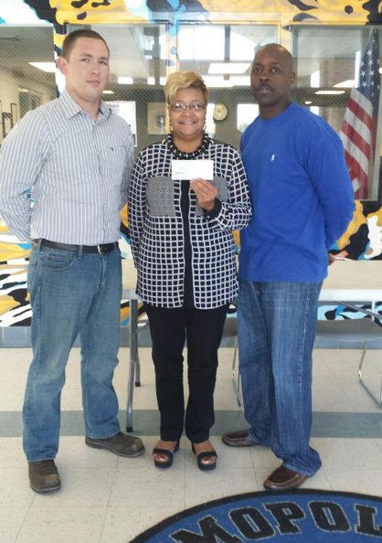 King (left) and Russell (right) present a check to Demopolis High School. The check was accepted by Assistant Principal Virginia Goodlett.