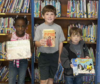 Milani O'Neal, Cameron Bell and Jacob Saelens are shown with some of U.S. Jones Elementary School's library books that are worn from use.