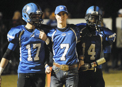 Wil Stephens (17) and Antonio Mackins (14) escort their injured teammate Jacob Browder out to midfield before Friday's game. Browder was named head captain for the game. He was injured in a bull riding accident earlier this fall.
