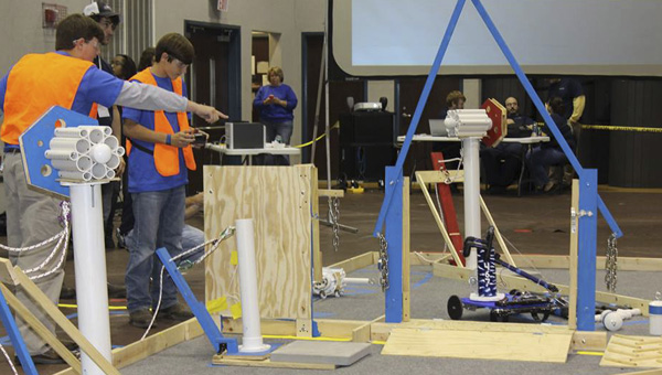 Jordan Durrett (right) spots for Chance McVay as he drives the Demopolis Robotics Team's robot in Saturday's BEST competition at Shelton State Community College.